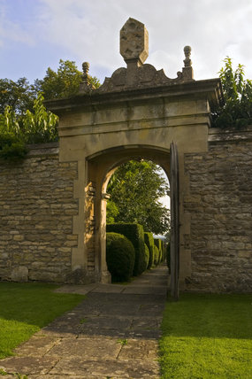 Dramatic stone entrance arch at Westwood Manor, near Bradford-on-Avon, Wiltshire, with a view to the topiary-flanked path leading from the road