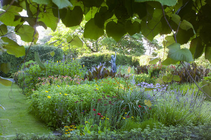 Colourful planting in the herbaceous borders of the Statue Garden at Overbecks Garden, Salcombe, Devon