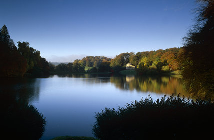 A mirror-like surface on the lake at Stourhead, Wiltshire with autumnal trees reflected in the water