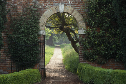 View through an arch in the garden at Felbrigg in the early morning in July