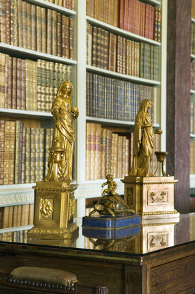 Ormolu figures on a table in the Library at Hinton Ampner, Hampshire