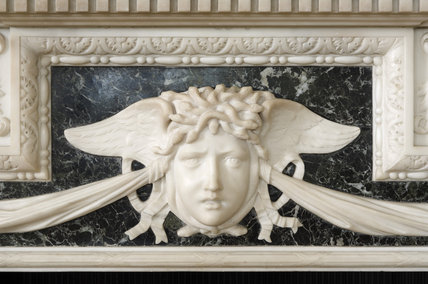 Close detail of the mythical face with snakes for hair on the black and white marble fireplace in the Old Dining Room at Mottisfont Abbey, Hampshire