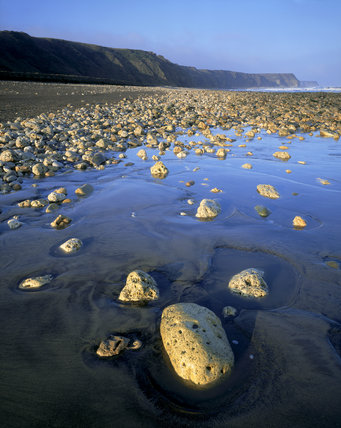 Horden Beach on the Durham Coast strewn with rocks in bright sunlight;the cliffs showing the effects of mining over the years in this area acquired by the Trust for reclamation