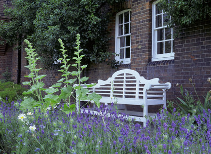 Lavender and hollyhocks with a garden bench in the garden of Red House designed for William Morris by Philip Webb in 1859, a red brick house laid in 'English Bond' with a red tiled roof