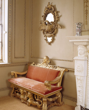 View of a girondole on the wall featuring a gilded bird with wings spread, and a William Kent gilt settee below, in the Ionic Temple on the Terrace at Rievaulx
