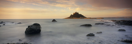 St.Michael's Mount seen across a misty rock strewn foreshore; it was originally a Benedictine Priory and is approached by a causeway at low tide and by boat at other times.