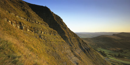 View of Mam Tor in Edale, part of the Peak District, Derbyshire, showing lateral gritstone extrusions on the cliff face, Lose Hill in the distance, Castleton and enclosed farm land in the valley below and a mixed background