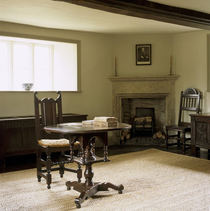 Room view of the Parlour at Woolsthorpe Manor showing the 17th century stone fireplace set across the angle of the corner of the room and 17th century oak furniture