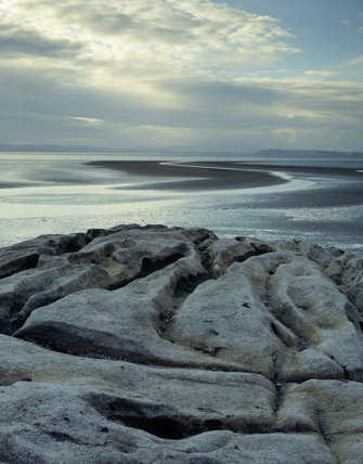 Looking across Morecombe Bay from Heysham Head with a limestone oucrop, the vast estuarial flats of the Bay at low tide and the central Lake District Fells in the far distance