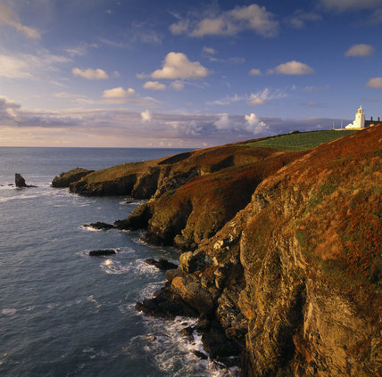 The Light House at the Lizard Peninsula in the dawn sun with Bumble Rock and the Lions Den