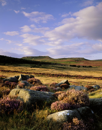 A cloud-dappled blue sky sharpens the outline of Hathersage Moor and Higger Tor viewed from open moorland north of Burbage Brook on the Longshaw Estate in the Peak District