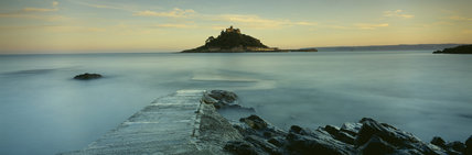 Panoramic view of the C12th castle on St Michael's Mount in silhouette, lit by the sun on its west side