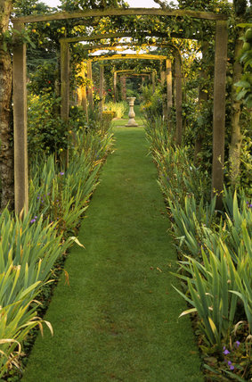 Long view through the Pergola at Gunby Hall, with a sundial in the mid-distance on a grassy path, iris leaves on either side