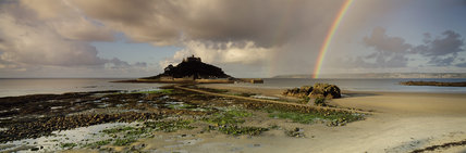 Panoramic view of the sea and rocky coastline around St. Michael's Mount, with its castle dating from 12th century. On one side is a rainbow, in front is a close view of the causeway