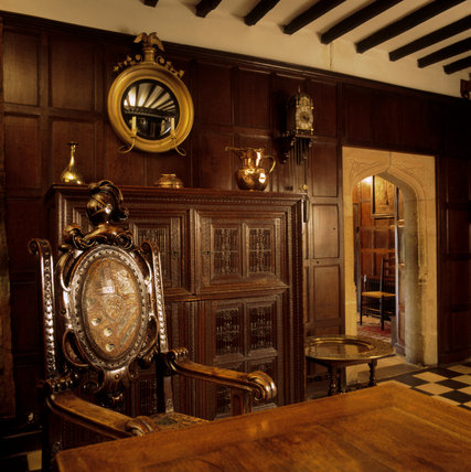 The Hall with a close-up of the oak Indo-Portuguese cupboard, with fine linenfold panels, Tibetan brass jug, 1630's brass lantern clock, mirror, small table and a C18th