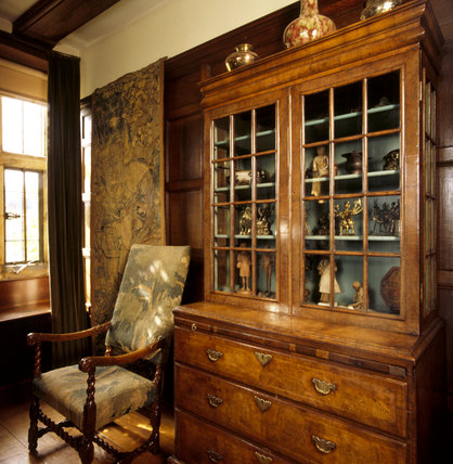 Close-up of the walnut bureau in the Parlour, containing Indian artefacts and works of art collected by Kipling