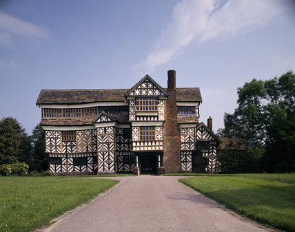 The outside of Little Moreton Hall, revealing its timber-framed structure with diagonal bracing and quatrefoils