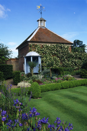 View of the Walled Garden at Gunby Hall in Summer, herbaceous borders laden with lavender, and blocks of dazzling flowers