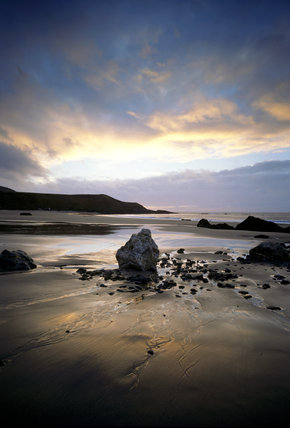 Jagged rock towering above the rock pools and pebbles of Porth Oer, a magnificent sunset in the sky