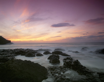 A sunset coastal view taken at the Giant's Causeway, with the sea in motion over the unusual rock formations