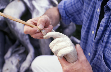 Using a spatula to model a finger of a damaged arm from a vandalised statue