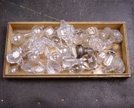 A tray full of glass stoppers, and one with silver, for decanters, in the Butlers Passage at Tyntesfield