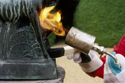 Detail of flame heating a surface of bronze before microcrystalline wax is applied to the hot metal