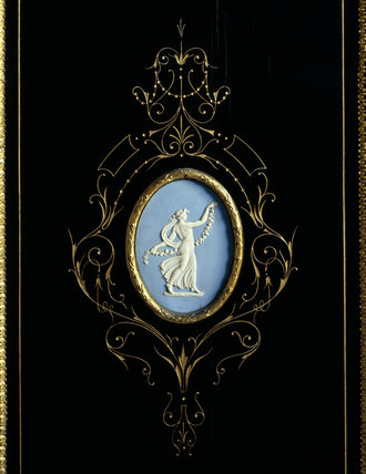 Close view of detail of an oval Wedgwood plaque with a classical female figure on an ebonised cabinet in the Drawing Room at Llanerchaeron
