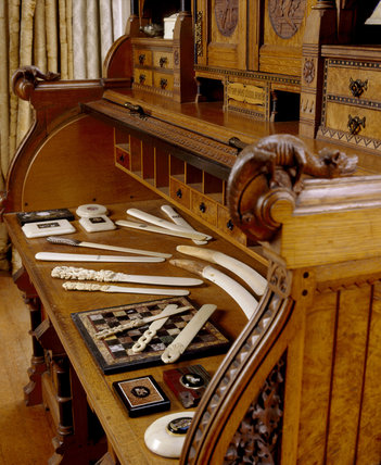 Close view of a Plucknett & Collier writing-desk, with its many drawers and compartments, displaying a selection of letter openers, & paperweights at Tyntesfield