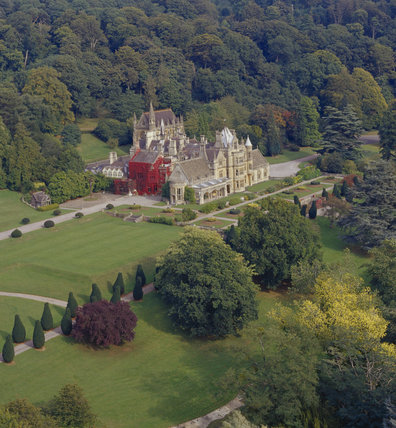 Aerial view of Tyntesfield showing South-west front & Chapel beyond, garden terrace with lawns & eight flowerbeds, central holly bushes & classical stone urns