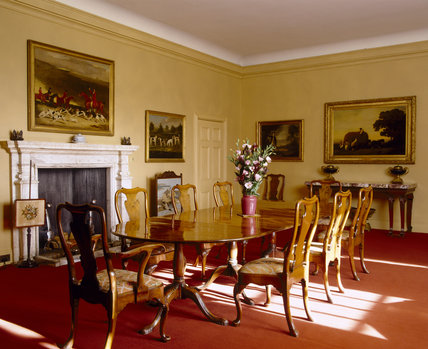 The Dining Room at Upton House with mahogany dining table and George I style walnut dining-chairs with seat covers embroidered by 3rd Lord Bearsted