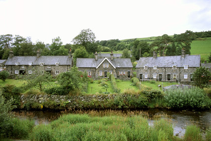 A view of the village of Ysbyty Ifan looking across the river Conwy to a group of stone houses with slate roofs, the river banks covered with wildflowers