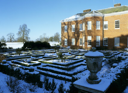 A view across the snow covered Jeykll Garden at Hatchlands, to the House
