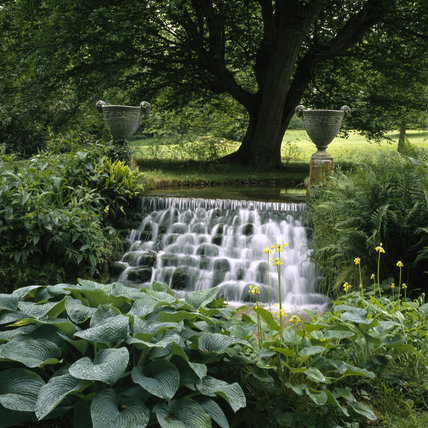 Waterfall and stone urns in the garden at Mottisfont Abbey in Hampshire