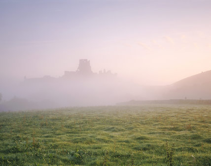 Corfe Castle seen through dawn mist