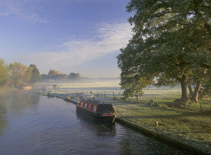 A narrowboat awaiting passage through Papercourt Lock, River Wey Navigation, on a bright & misty autumnal morning with walkers in the background
