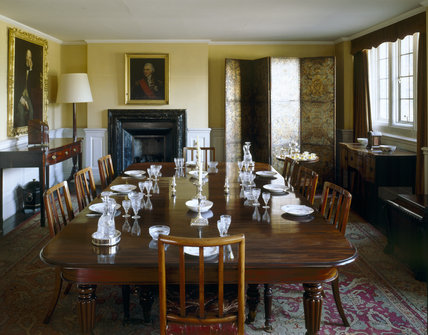 the small dining room with the table set with plates