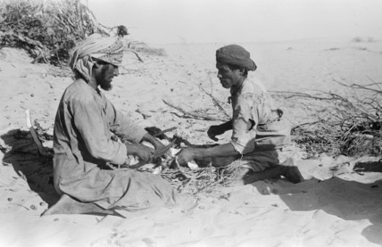 Arab men cutting up meat