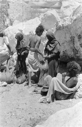 Mahra people filling water skins at Sarif well