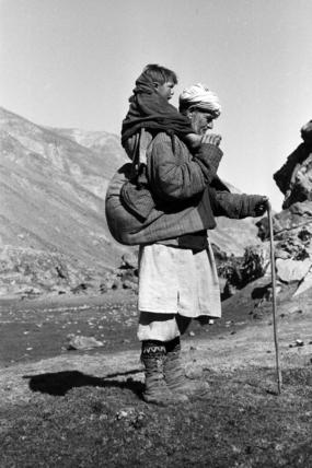 Tajik man carrying a boy on his back