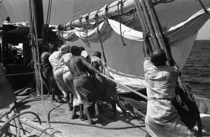 Sailors raising the mainsail
