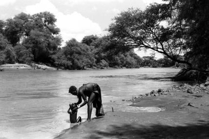 Turkana woman bathing her child