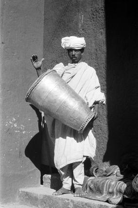 Debtara playing a silver church drum