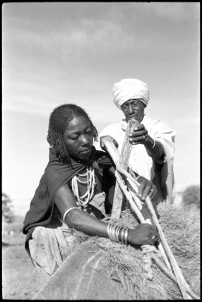 Boran woman fitting a saddle on a camel