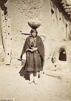 Zuni woman carrying a pottery vessel