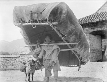 Man carrying hide boat by Yuthok bridge