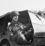Sergeant Norman Midgley, a photographer with No. 5 Section of the Army Film and Photographic Unit, in a jeep during the battle for Caen in Normandy, 24 July 1944.