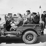 Winston Churchill lights a cigar in the back of a jeep while touring the Normandy beaches with General Mongomery, 12 June 1944.