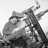 A Bofors gunner writing a Christmas card for home, Holland, 8 December 1944.