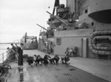 Sailors scrubbing the deck on board HMS RODNEY, 1940.